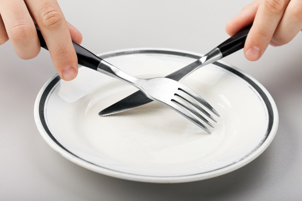 A person holds a knife and fork over an empty plate. Intermittent fasting can increase BDNF levels.