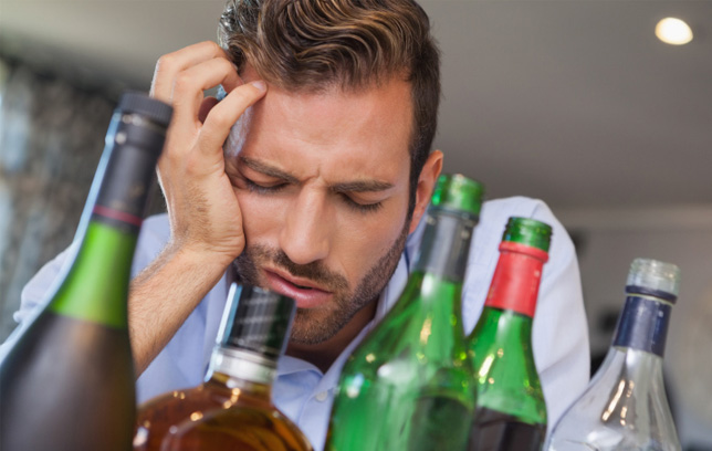 Man hungover in front of several bottles of alcohol.