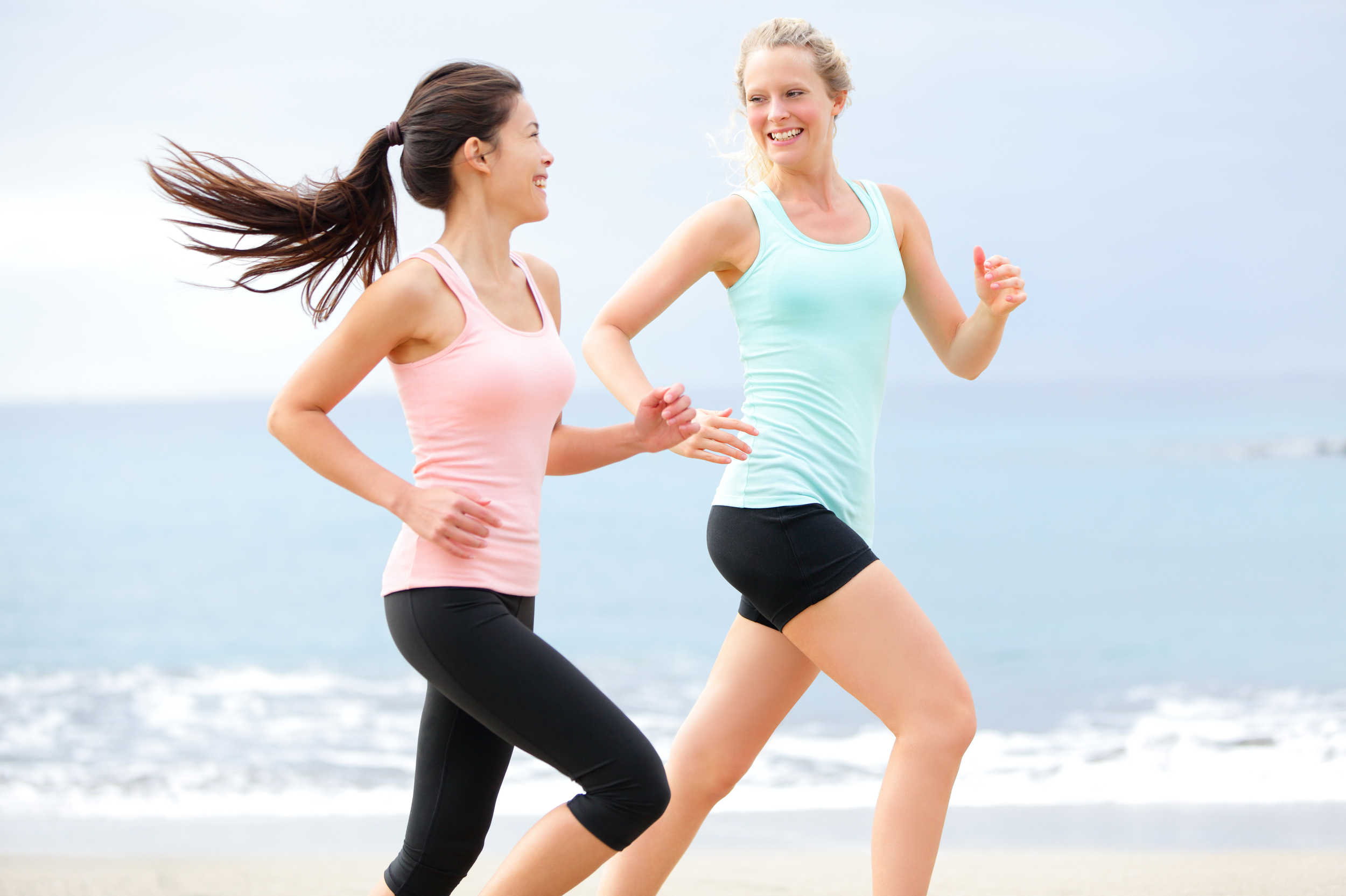 Two women running on the beach. Exercise can help reduce brain fog. Too much exercise can cause brain fog though.