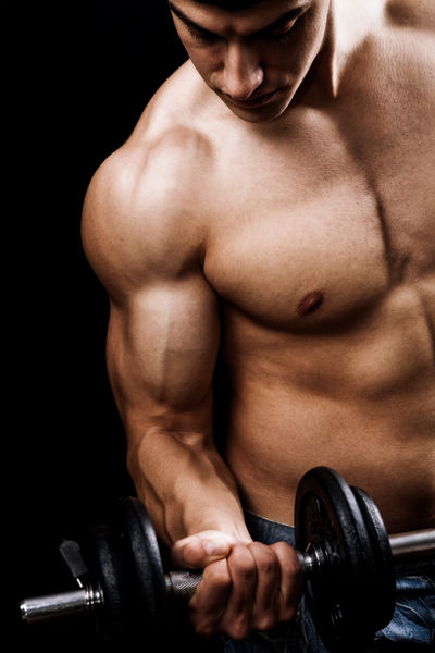 A muscular man lifting weights. Testosterone can help with brain fog.