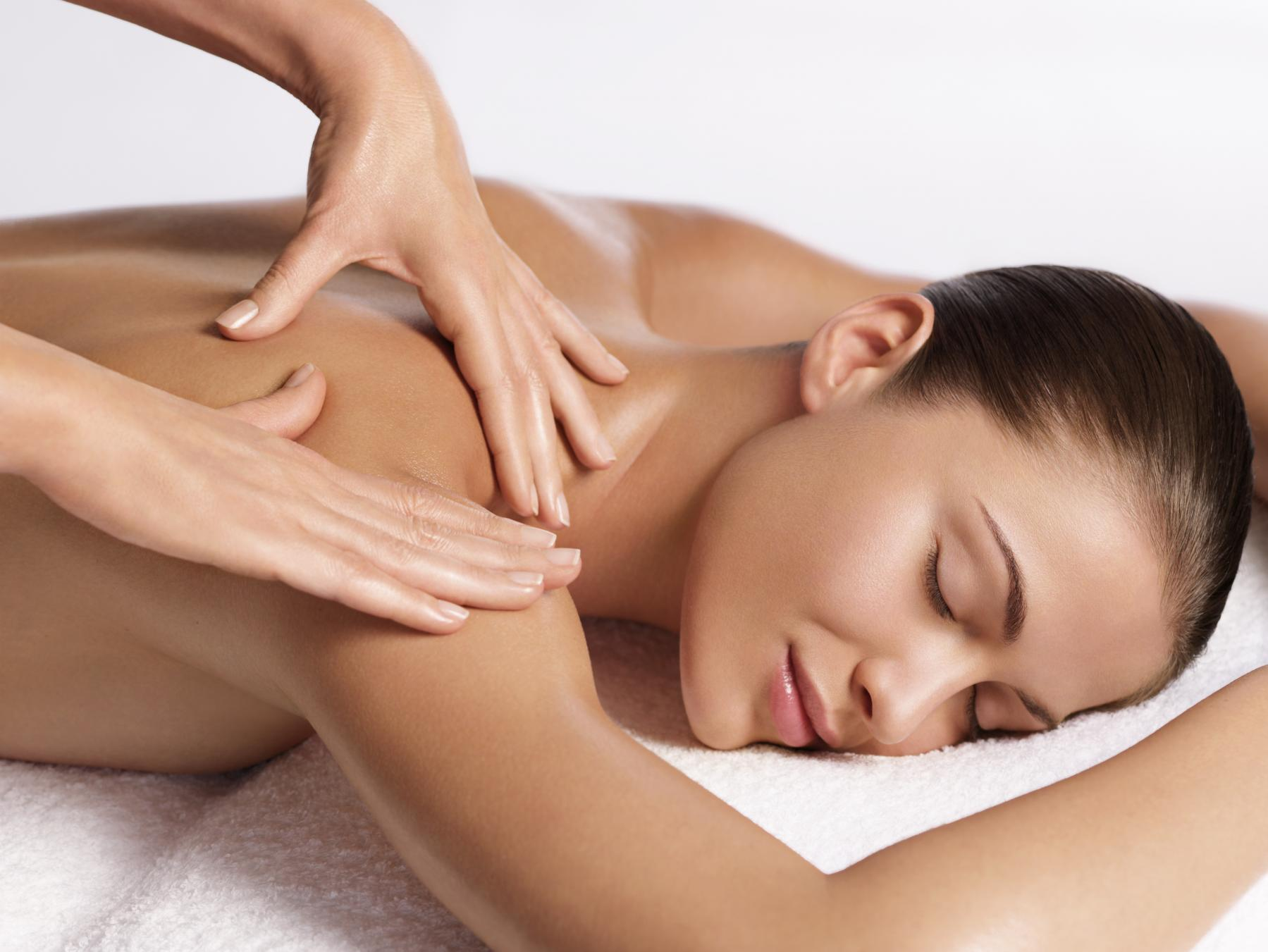 A woman is lying down and getting a massage/ Massages can lower your cortisol levels.