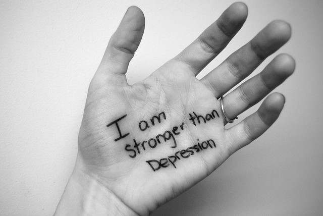 "A person's hand and it says ""I am stronger than depression."""