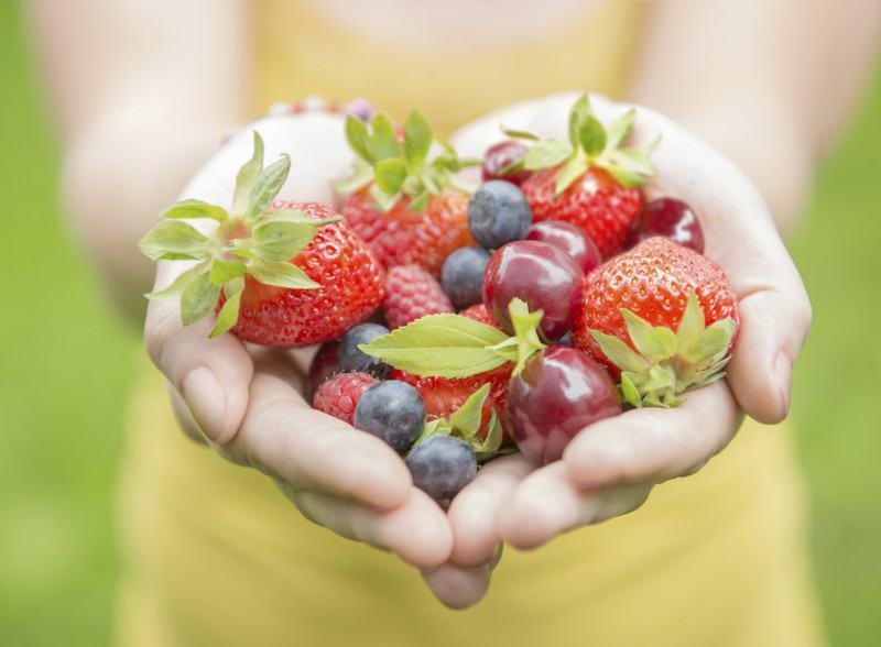 A woman holding a handful of berries.