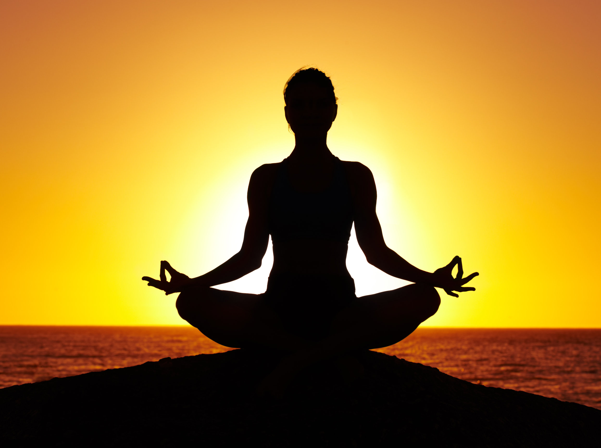A woman meditating outside while the sun sets. Meditation and reducing stress can help prevent and reverse dementia and cognitive decline.