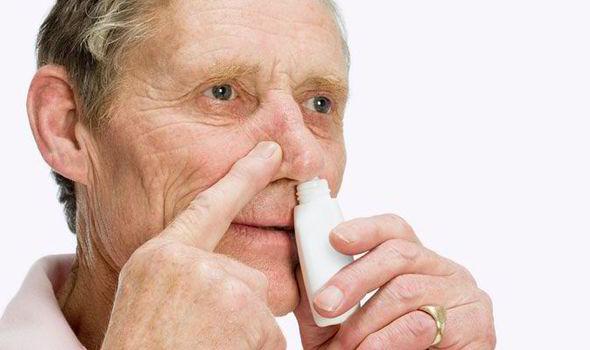 An elderly man sprays intranasal insulin up his nose.