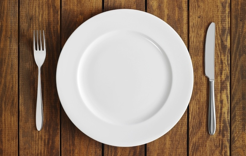 An empty plate with a fork and knife beside it. Intermittent fasting stimulates the vagus nerve.