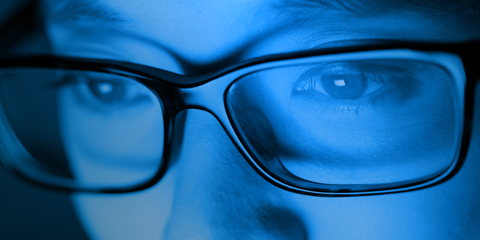 A woman staring at a screen and being exposed to blue light at night. She is wearing glasses, but they don't look like they block out the light!