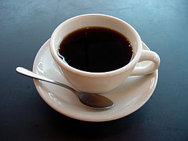 A cup of coffee on a plate with a spoon. Coffee supports and boost the endocannabinoid system.