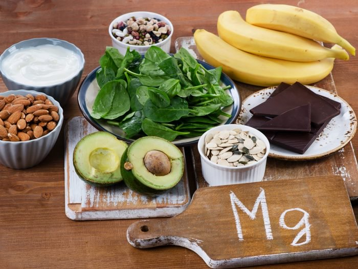 Magnesium-rich foods on a table, including avocados, bananas, almonds, spinach, dark chocolate, etc. A magnesium deficiency can make you more anxious.