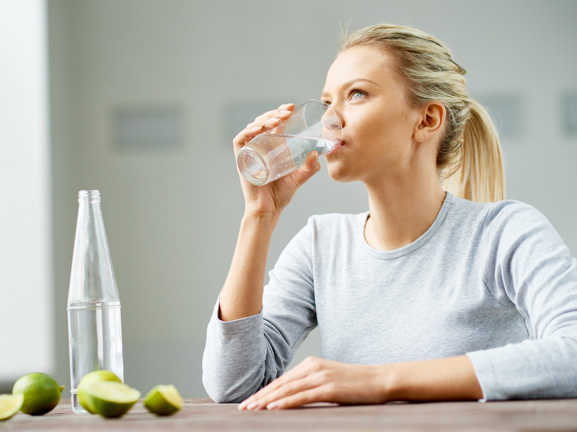 A blond-haired woman drinking a glass of water. Intermittent drinking increases oxytocin levels in the brain.