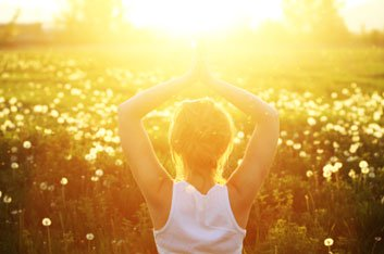 Woman looking towards the sun. Sunlight can increase dopamine levels in the brain.