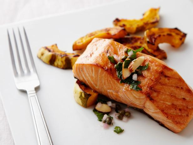 A piece of cooked salmon on a plate and a fork. Salmon contains omega-3 fatty acids that increase dopamine in the brain.