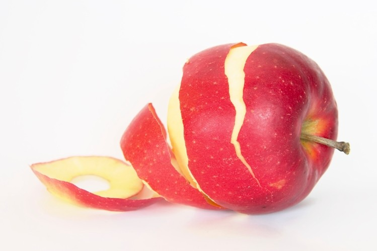 An apple partially peeled. Apple peels contain ursolic acid, a natural compound that can increase IGF-1 levels.