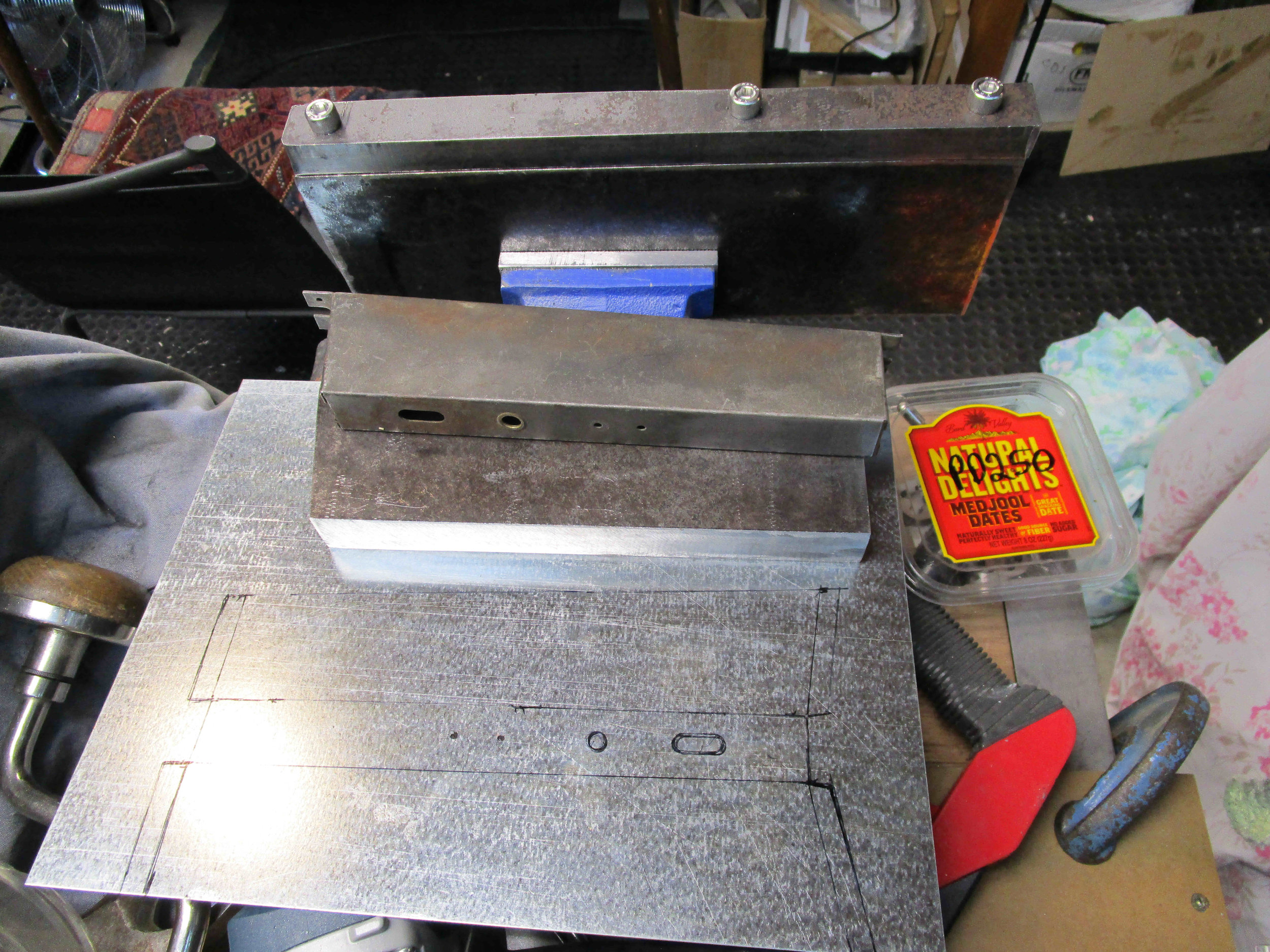 Marking out tin plate using template. Original box shown in centre.