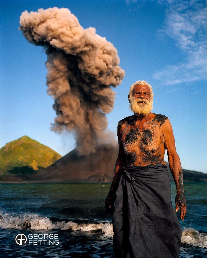 Local elder Ken Kolias and Tavurvur the volcano venting Rabaul PNG.