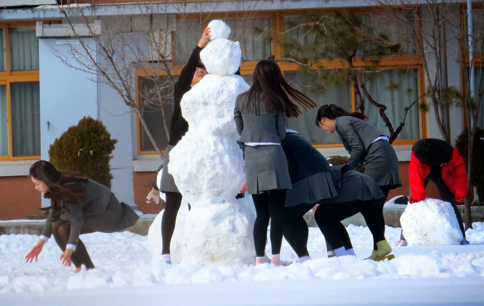 KOREA - Students building a snowman over lunch break