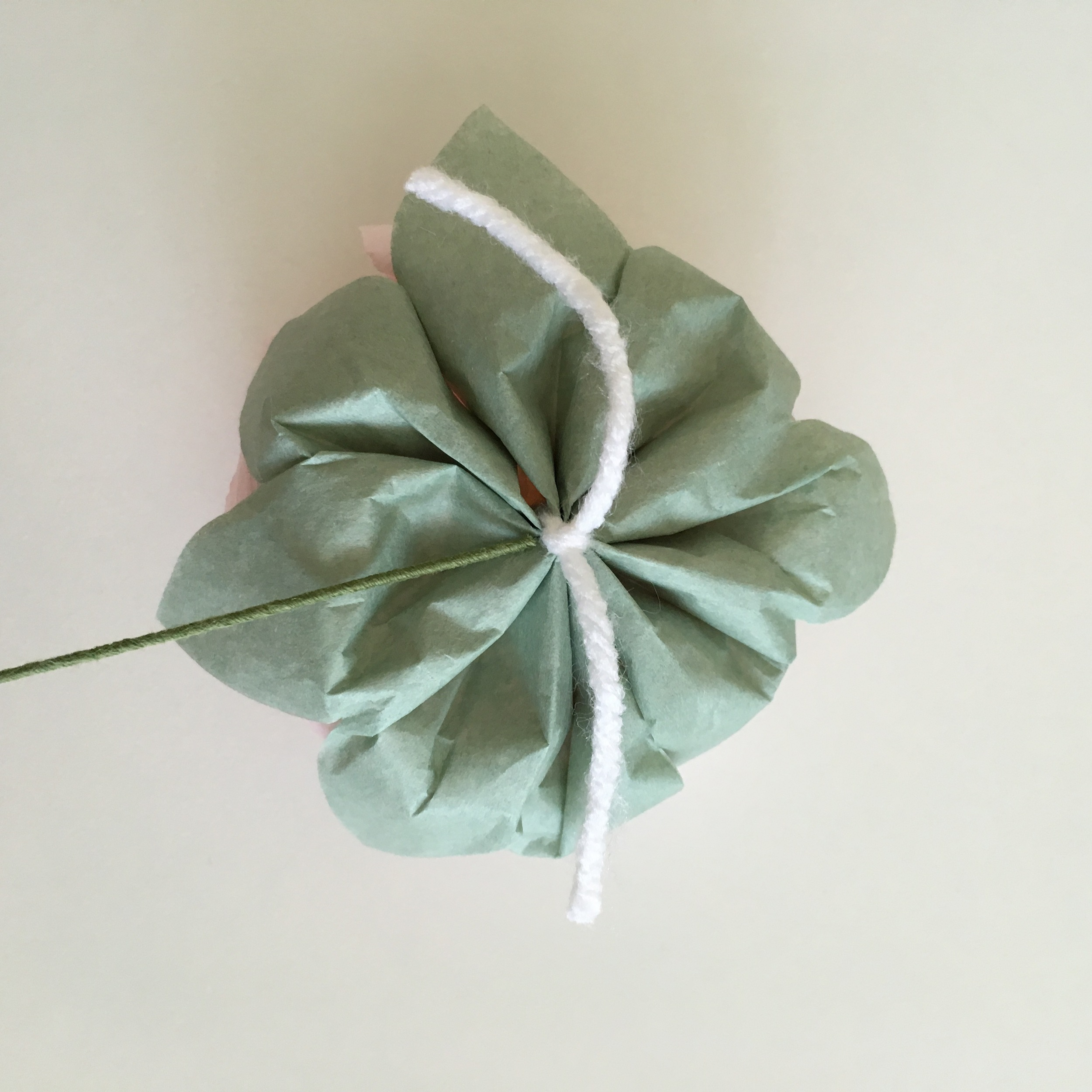 8. Holding the yarn knot, poke the floral wire through the opening between the knot and the paper flower.