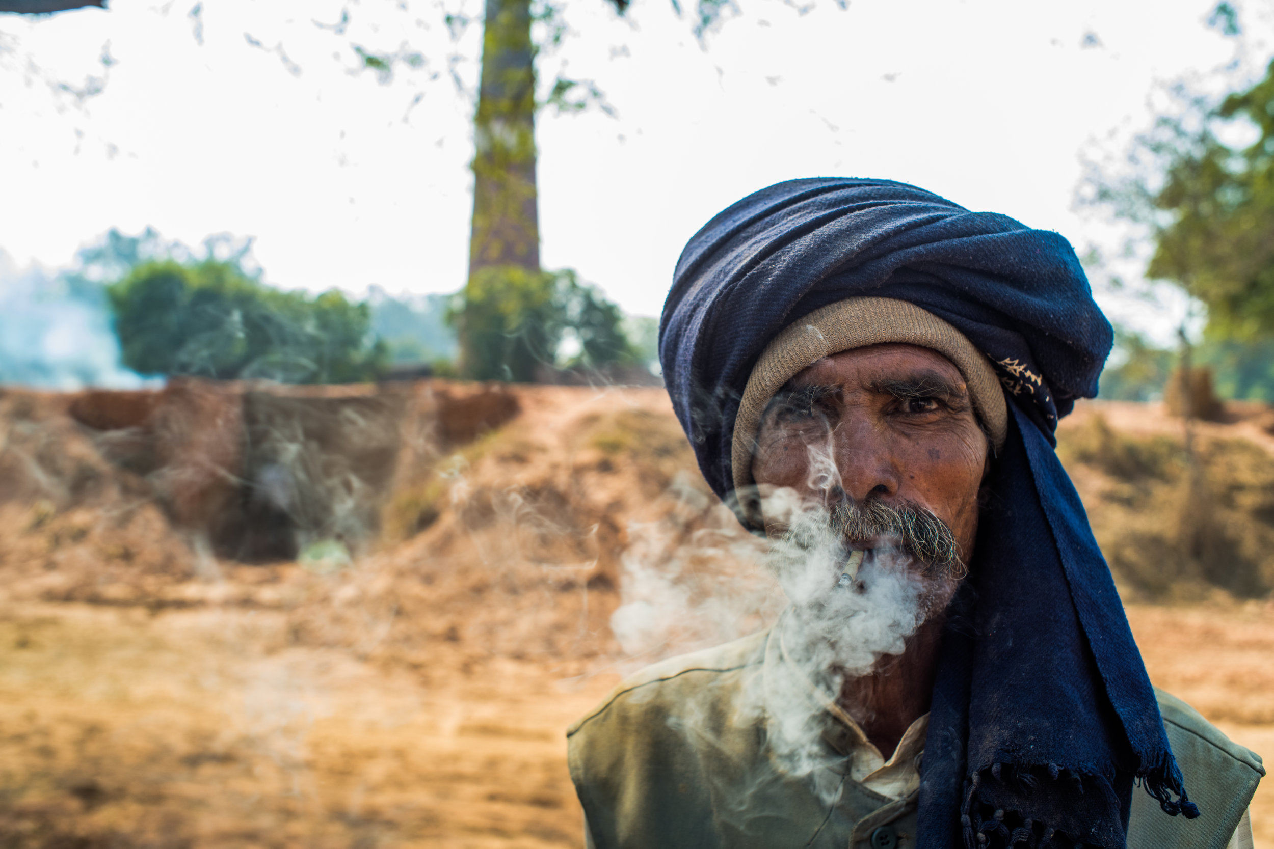 A man takes a break from working at a brick kiln outside of New Delhi, India.