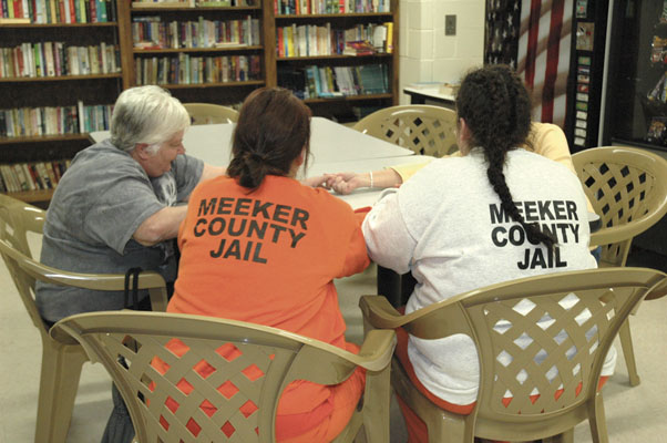On a Friday afternoon in mid-April, Jayne Otley and Carol Schumacher visit with two inmates in the Meeker County Jail library. A pair of Encouragement Klatch Ministry volunteers meets with female inmates at the facility weekly. Part of the shared experience involves praying together, during which time hands are held. (Photo by Claudia Broman)