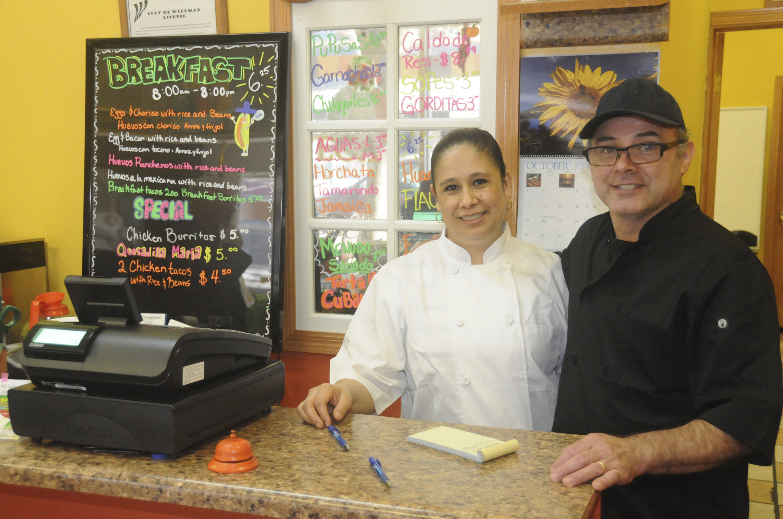 Guillermina Serrano and her husband, Salvador, stand behind the counter of Azteca Mexican Restaurant on Fourth St. SW in downtown Willmar on Oct. 14. The couple operates the restaurant with two children, Guillermo and Ana. To ensure the success of their fledgling restaurant, the family receives subsidized rent and business advice from the Willmar Area Multicultural Business Center. WAM-BC, in turn, receives financial support from the Catholic Campaign for Human Development.                                (Photo by Dan Rossini)