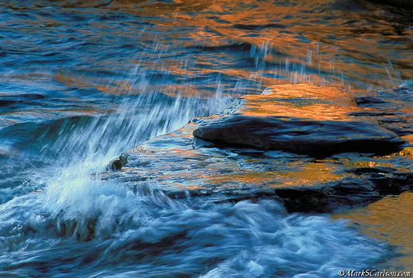 Lake Superior waves splashing over rocks with autumn reflections; ©markscarlson.com