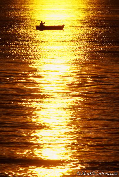 Fisherman in sunset reflection on Lake Superior; ©markscarlson.com