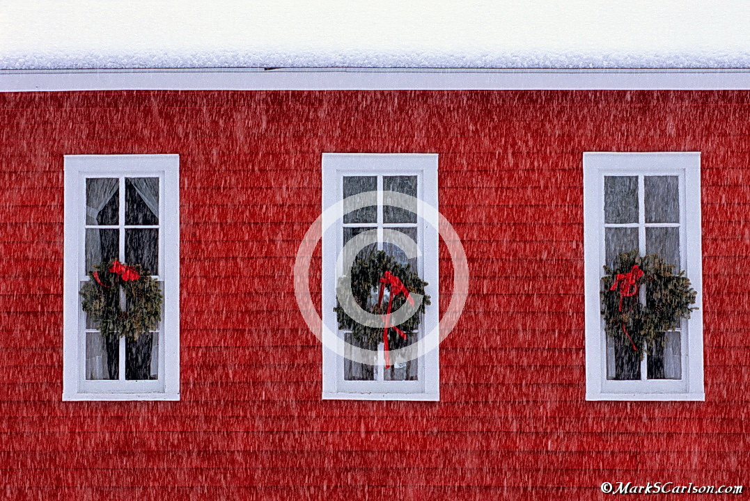 Three windows with holiday wreaths, red schoolhouse with falling snow; ©markscarlson.com