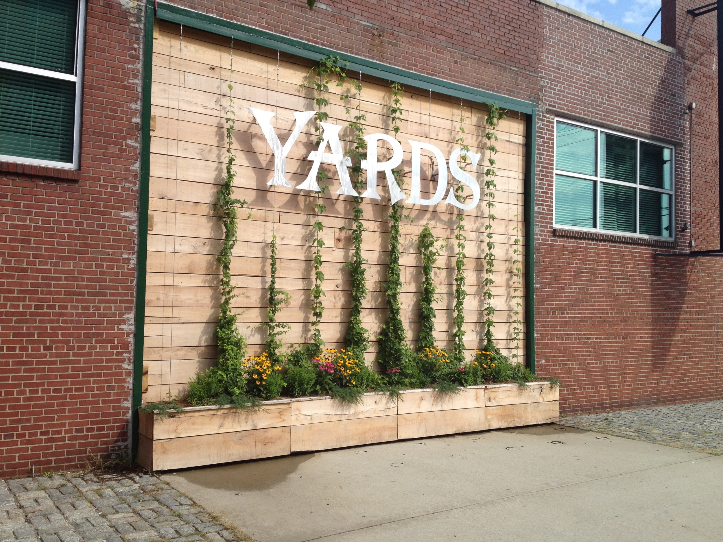 Sign and planters with hops.