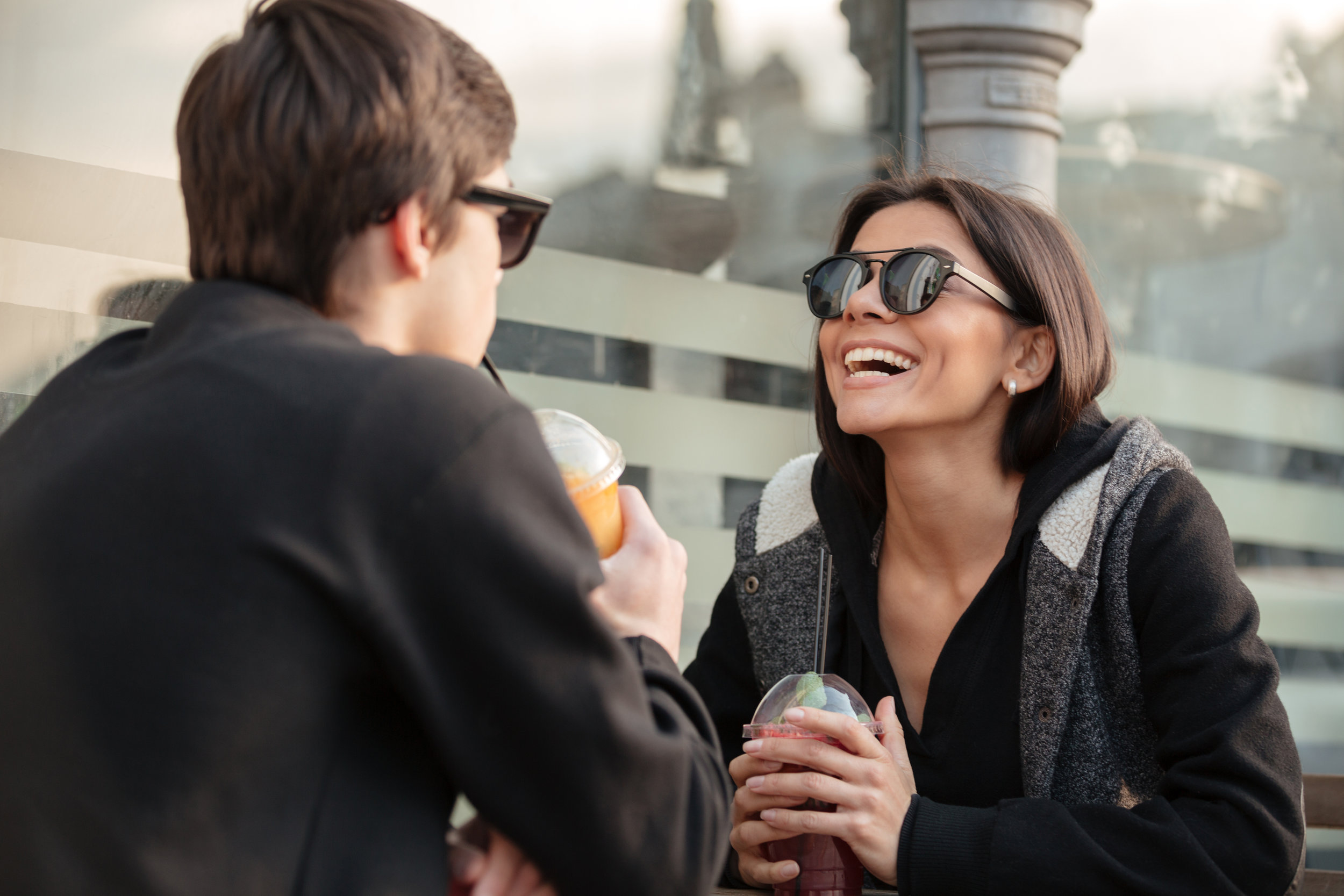 woman laughing drinking a smoothie
