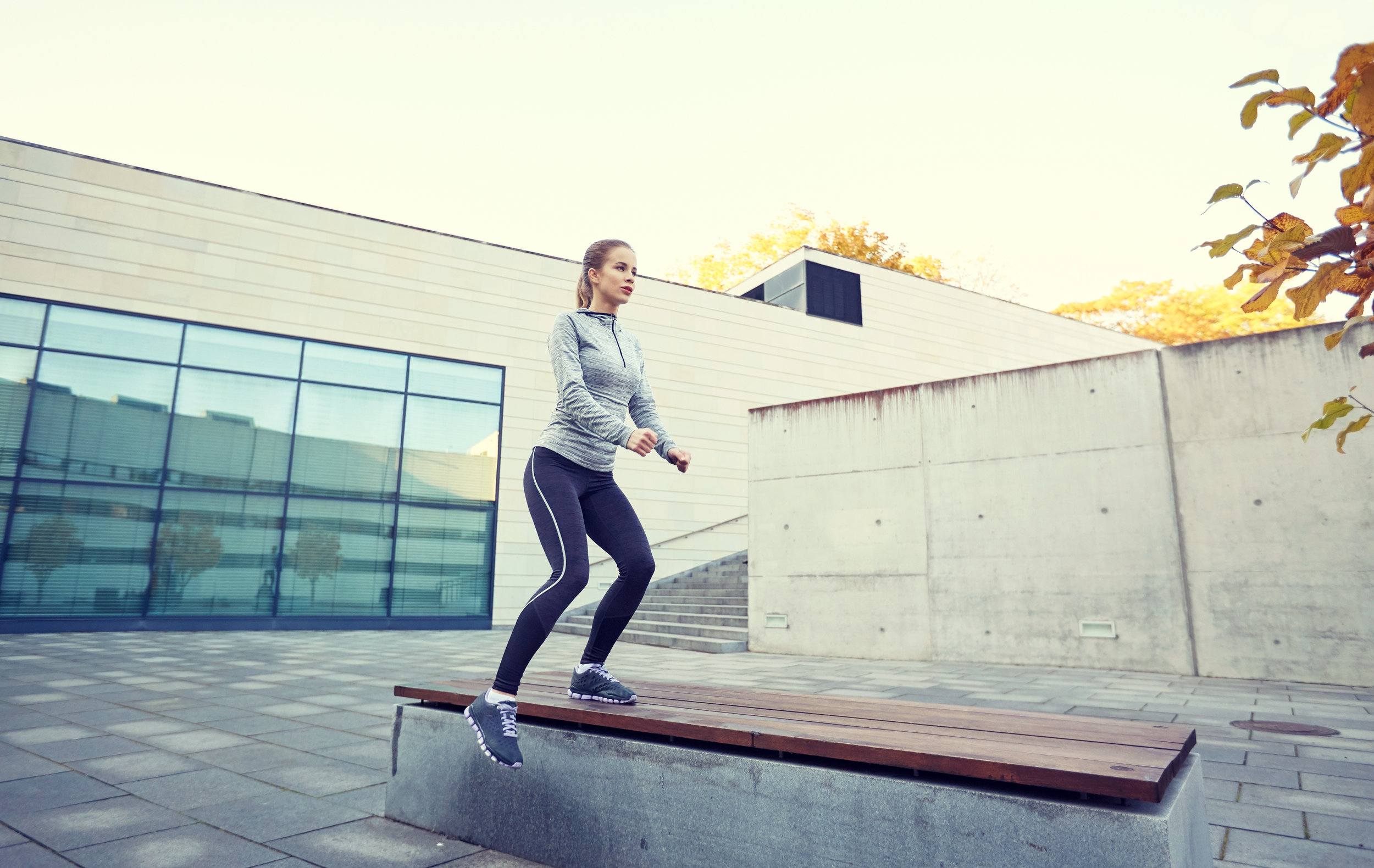 woman-exercising-on-bench-outdoors-PHVLWHS.jpg