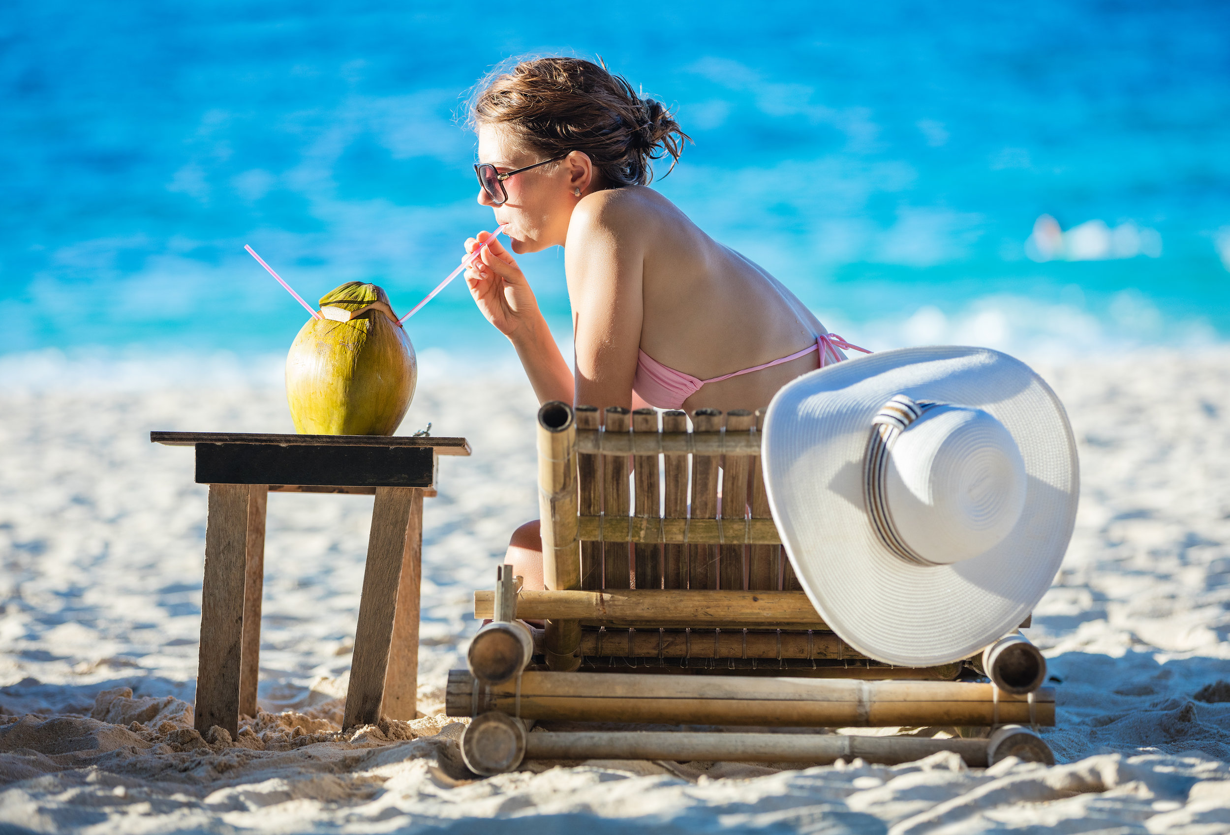young-woman-drinking-coconut-juice-while-relaxing-PWARWFQ.jpg