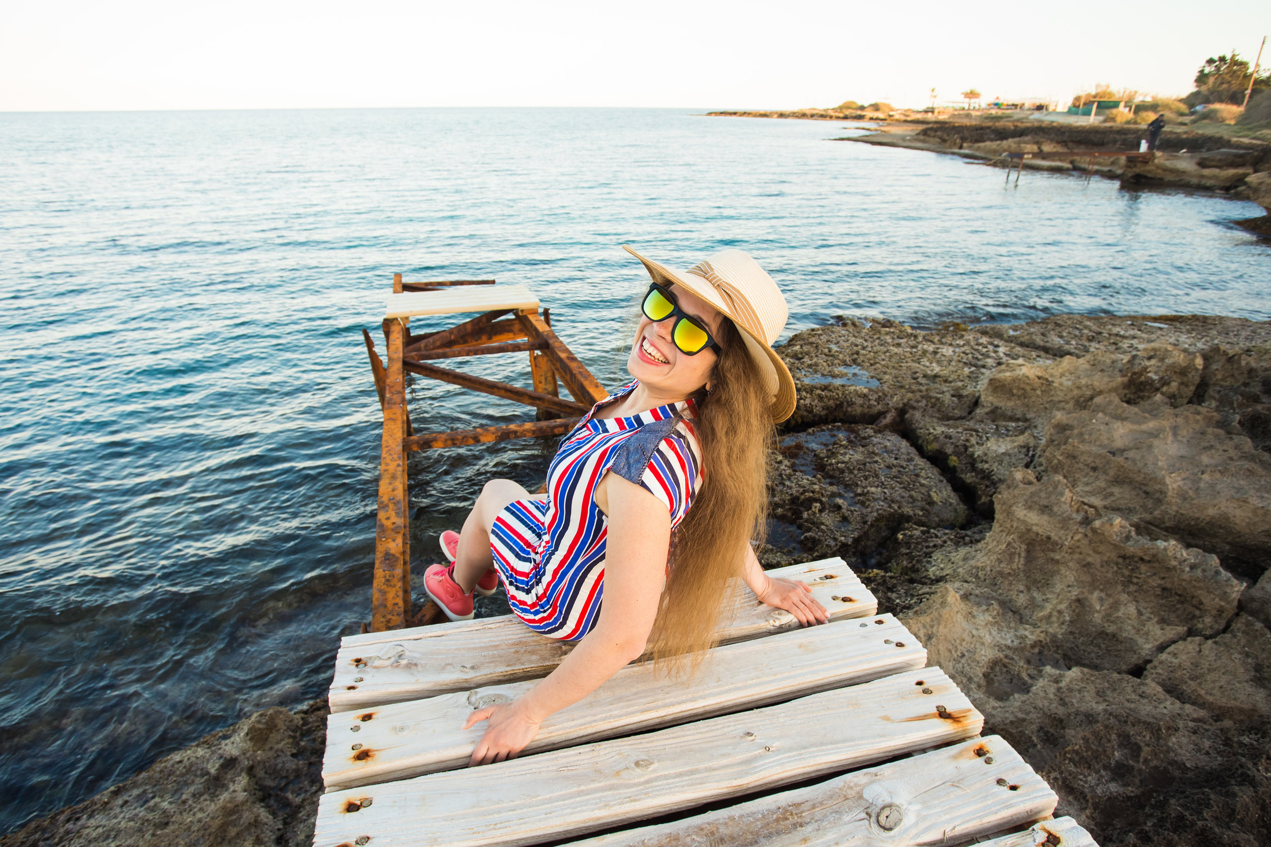 young-happy-woman-sitting-on-wooden-pier-and-PR55BKH.jpg