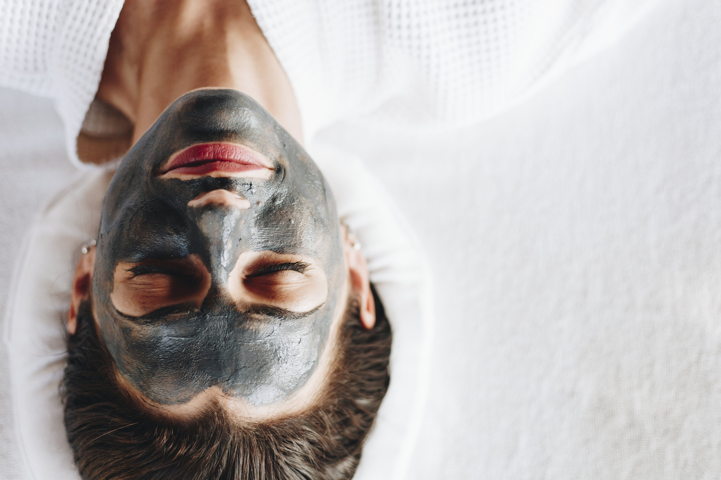 woman-relaxing-with-a-charcoal-facial-mask-QXUBHGR.jpg
