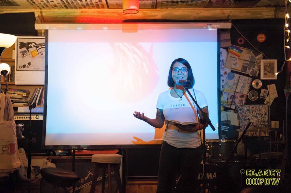 Christina Romero reciting poetry at An Art Show, 69 Cafe