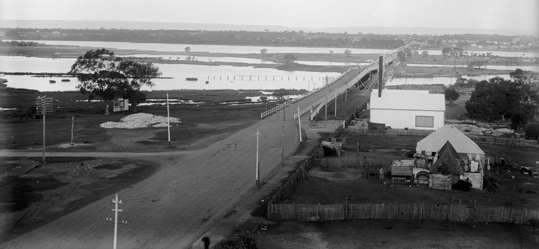 The second Causeway was built in response to the flooding which had occurred in June 1862. Designed by colonial architect Richard Roach Jewell, the Causeway was reconstructed several feet higher than the original, using convict labor. It was officially opened, along with the Guildford and Helena bridges the same day, by WA Governor John Stephen Hampton on 12 November 1867. The Causeway was originally to be opened by HRH Prince Albert, Duke of Edinburgh in a grand affair but due to the Duke's royal yacht failing to dock at Fremantle harbor, the Governor took his place in the proceedings.  Consisting of three bridges totaling 490 metres, the second Causeway was structurally weak for its time due to budget constraints and required numerous upgrades throughout the years. The bridges were strengthened and their width increased on three separate occasions in 1899, 1904, and 1932 respectively, culminating in a total width of 11 metres. The second Causeway stood proud for 80 years until it was replaced by the current dual Causeway bridges that connect Perth to Victoria Park via Heirisson Island in 1947. Pictured above, the second Causeway bridge looking east to Victoria Park, 1905. (Supplied: State Library of Western Australia)