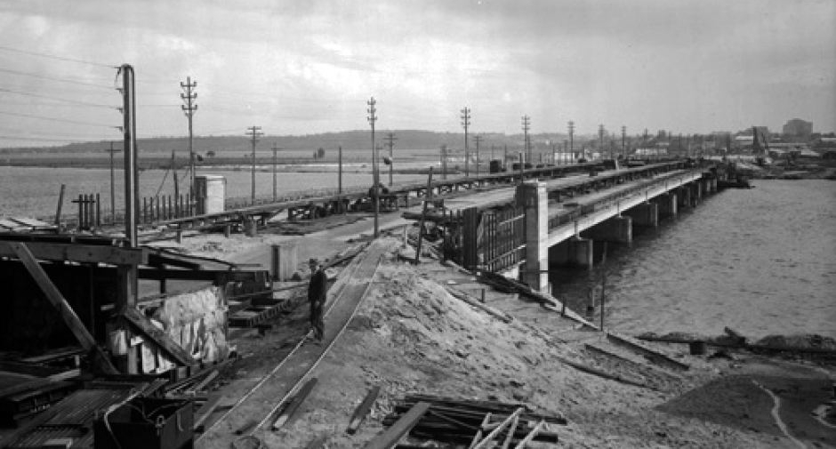Traffic over the Causeway had doubled between 1931-1939, prompting calls for a new, larger bridge to be constructed on the site. Due to the outbreak of the Second World War, both construction of the Narrows Bridge, and the Causeway were delayed until the mid 1940s when development began for the third iteration of the Causeway bridges in 1947. Designed by E. W. C. Godfrey, they were only the second bridges in Australia to use steel composite construction, and required significant dredging to widen navigation channels either side of Heirisson Island, which was converted from two separate islands into the singular one we know today.  The bridges have a combined length of 341 metres and stand 19 metres wide. Because of steel and concrete shortages due to the war, the piles for the support columns were made of jarrah timber, not concrete, and the design avoided the use of costly steel plate girders wherever possible. The concrete used on the superstructure was sourced from seven different locations, meaning the Causeway has differing durability at certain points along each bridge. Pictured above, the current Causeway under construction, 1951. (Supplied: State Library of Western Australia)