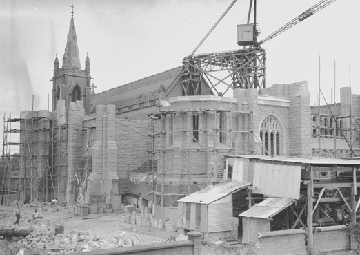 During the interwar years, the desire for a larger cathedral grew, culminating in 1924 when the first designs were submitted. Architect Michael Cavanagh's winning concept saw the majority of the original building being converted into the nave of the much larger cathedral, with the addition of a new sanctuary and a large Academic Gothic transept to be added to the eastern side. The foundation stone was laid on 25 April 1926 and construction continued for four years until, due to the onset of the Great Depression, the scope of the project was reduced and the works were completed in 1930. The unfinished design was opened to the public on 4 May 1930. Pictured, construction works in 1929 (Supplied: State Library of Western Australia)