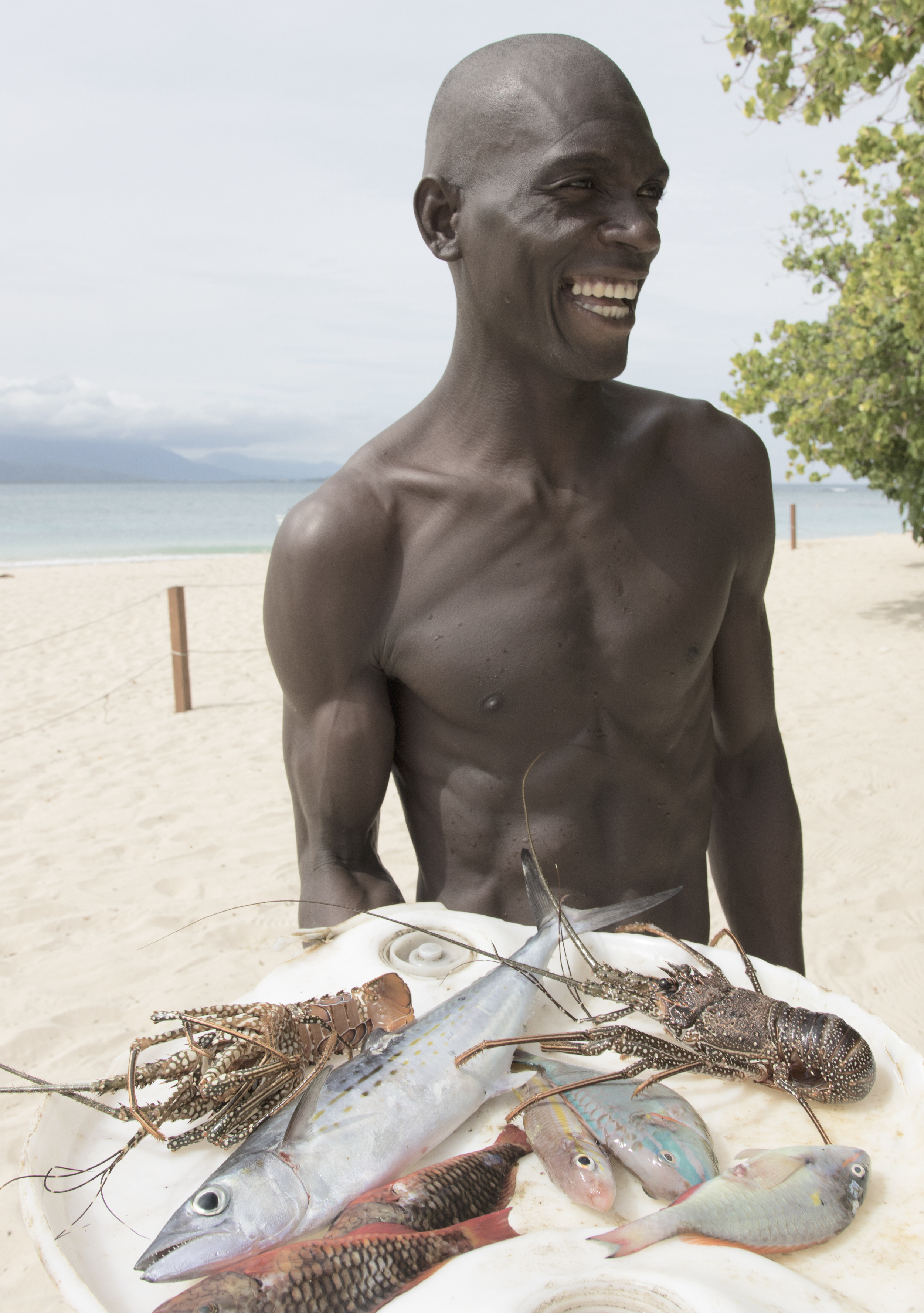 A FISHERMAN SHOWS OFF HIS CATCH AT AMIGA ISLAND, NORTHERN HAITI.