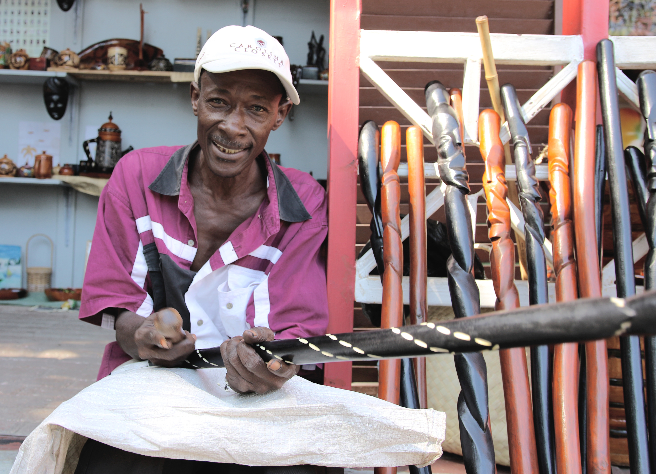 AN ARTISAN CARVES WOOD AND SELLS HIS WORK IN PORT-AU-PRINCE.