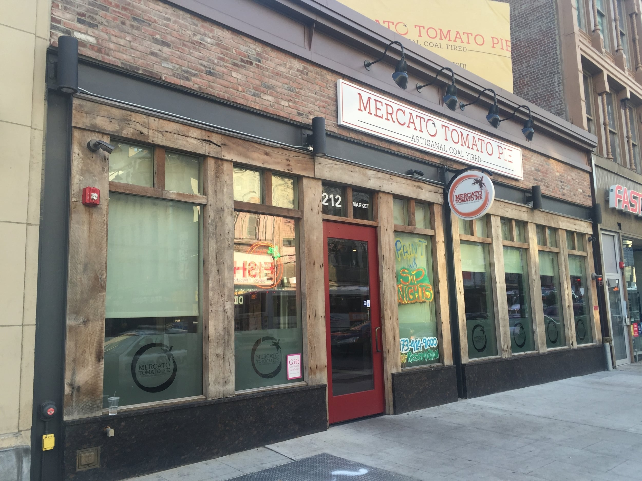 Mercato Tomato Pie, Market Street, Newark  uses all earth tones, a unique rustic wood and brick facade, goose neck lighting, accent lighting, and wall and projecting signs that match the facade. The business also used paint to advertise on the windows, further adding to its unique and artsy vibe.