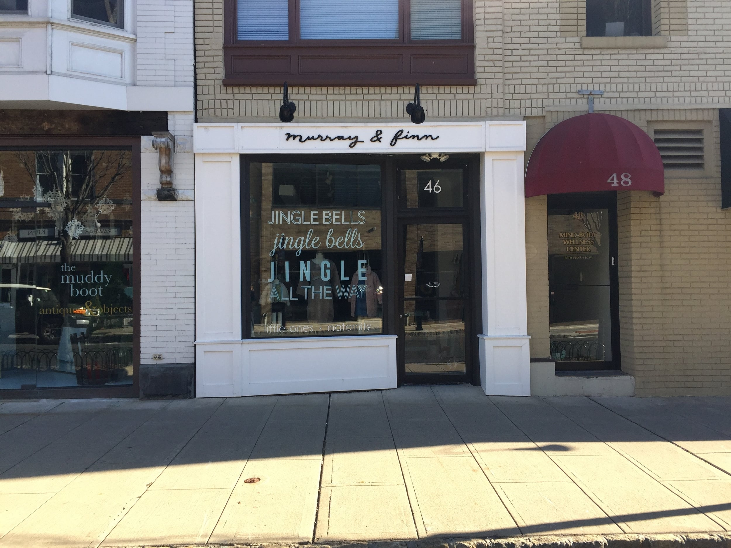 Murray & Finn, Summit  uses adhesive lettering instead of solid signage that blocks the storefront window. This is especially important for stores such as this one that has a small display window area.