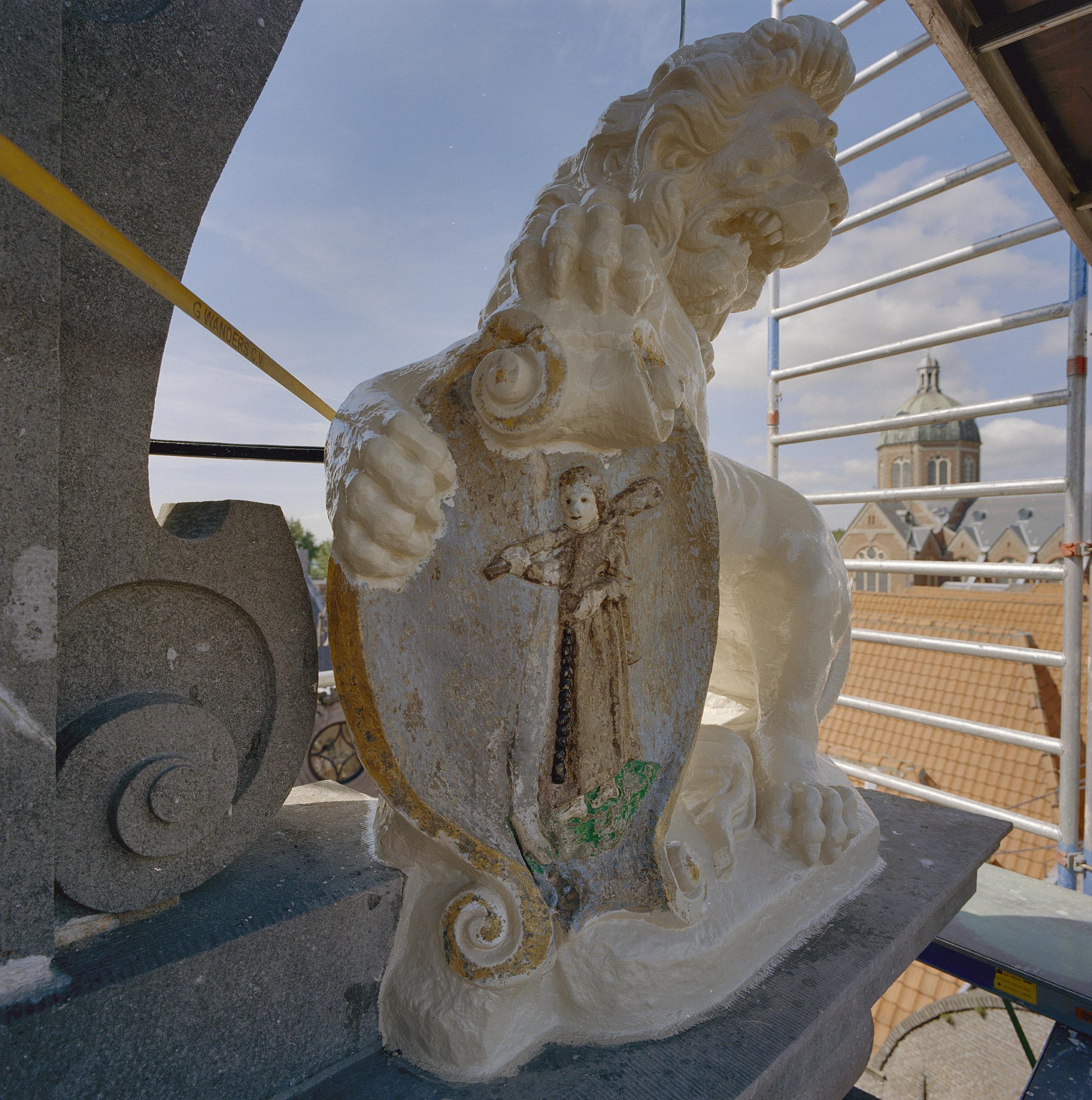 Beeldhouwwerk van een leeuw met een schild gesitueerd aan de voorgevel.