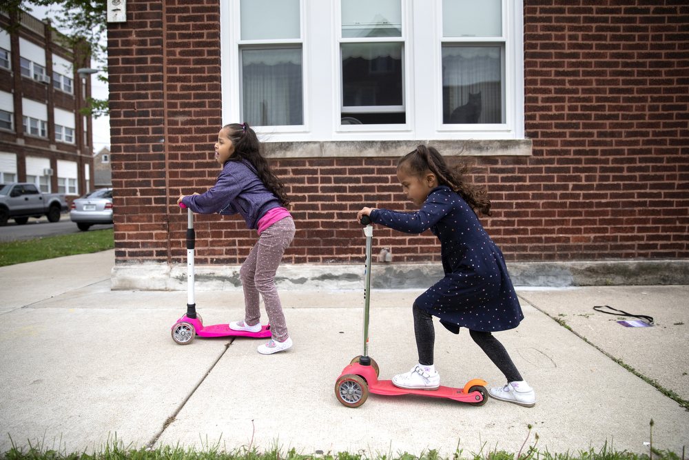 Skarleth Fernandez Flores, 6, right, and her sister Perla Flores Delgado, 3, play on scooters outside the home of the DeMay-Gres family, who is sponsoring their family as they seek asylum status in the United States, Sunday, May 20, 2018, in Chicago. The family left their home country of El Salvador years ago due to gang violence, living in Guatemala for awhile before ending up in Mexico. They crossed the border into the United States as part of a caravan of hundreds of people, organized by Pueblo Sin Frontreras, where they surrendered and sought asylum. Pueblo Sin Frontreras worked with Showing Up for Racial Justice, a national network of activists, to find sponsor families to house those in the caravan who did not have relatives in the United States. (Erin Hooley/Chicago Tribune)
