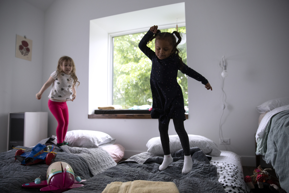 Perla Flores Delgado, 3, right, jumps on mattresses with Maggie DeMay-Gres, 4, at the home of the DeMay-Gres family, who is sponsoring her family as they seek asylum status in the United States, Sunday, May 20, 2018, in Chicago. The family left their home country of El Salvador years ago due to gang violence, living in Guatemala for awhile before ending up in Mexico. They crossed the border into the United States as part of a caravan of hundreds of people, organized by Pueblo Sin Frontreras, where they surrendered and sought asylum. Pueblo Sin Frontreras worked with Showing Up for Racial Justice, a national network of activists, to find sponsor families to house those in the caravan who did not have relatives in the United States. (Erin Hooley/Chicago Tribune)
