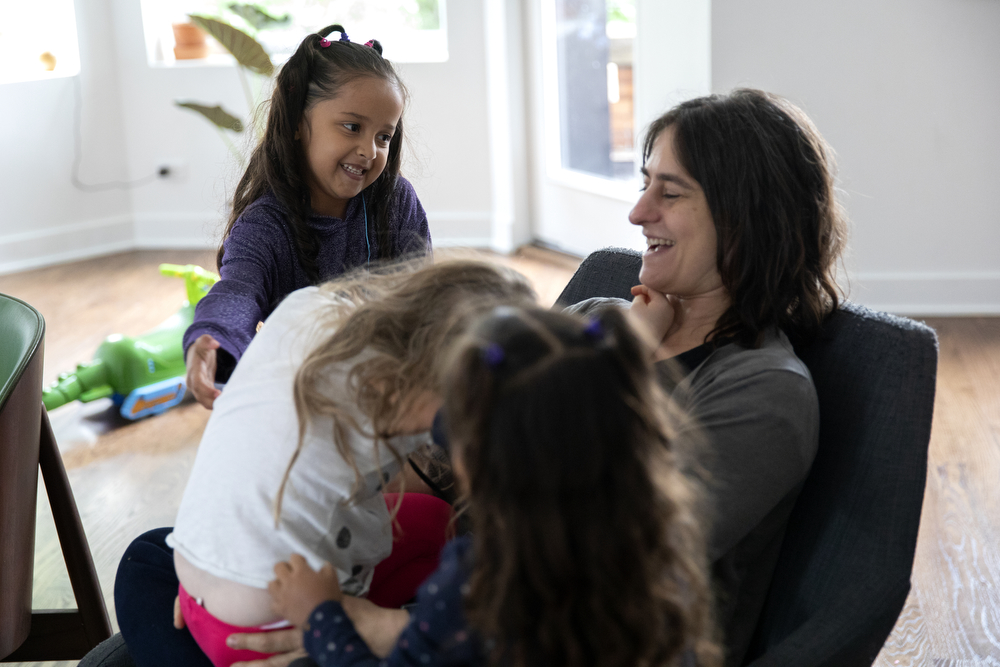 Skarleth Fernandez Flores, 6, left, looks at Liz Gres as she plays with Maggie DeMay-Gres, 4, at the home of the DeMay-Gres family, who is sponsoring her family as they seek asylum status in the United States, Sunday, May 20, 2018, in Chicago. The family left their home country of El Salvador years ago due to gang violence, living in Guatemala for awhile before ending up in Mexico. They crossed the border into the United States as part of a caravan of hundreds of people, organized by Pueblo Sin Frontreras, where they surrendered and sought asylum. Pueblo Sin Frontreras worked with Showing Up for Racial Justice, a national network of activists, to find sponsor families to house those in the caravan who did not have relatives in the United States. (Erin Hooley/Chicago Tribune)