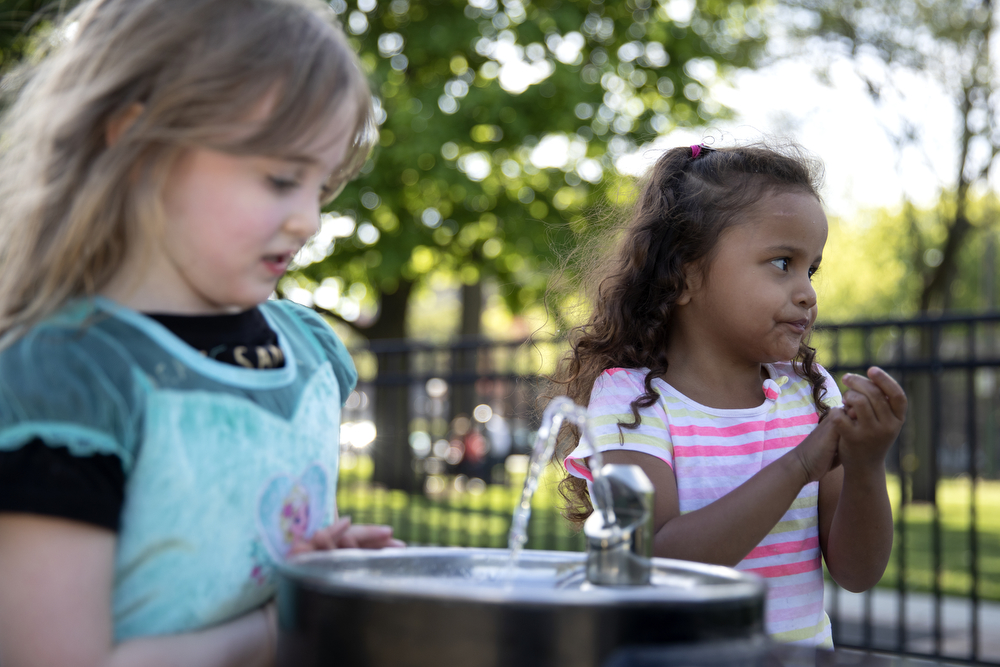 Maggie DeMay-Gres, 4, left, and Perla Flores Delgado, 3, get water from a fountain at Dunbar Park Wednesday, May 23, 2018, in Chicago. The Flores family left their home country of El Salvador years ago due to gang violence, living in Guatemala for awhile before ending up in Mexico. They crossed the border into the United States as part of a caravan of hundreds of people, organized by Pueblo Sin Frontreras, where they surrendered and sought asylum. Pueblo Sin Frontreras worked with Showing Up for Racial Justice, a national network of activists, to find sponsor families, like the DeMay-Gres family in Chicago, to house those in the caravan who did not have relatives in the United States. (Erin Hooley/Chicago Tribune)