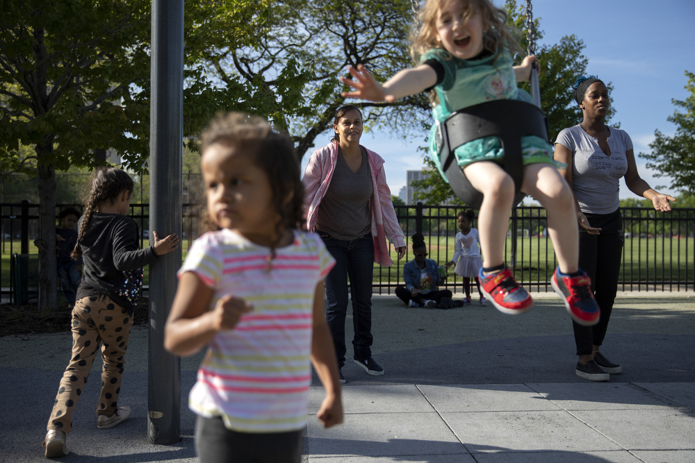 Maritza Flores pushes Maggie DeMay-Gres, 4, on a swing at Dunbar Park Wednesday, May 23, 2018, in Chicago. The Flores family left their home country of El Salvador years ago due to gang violence, living in Guatemala for awhile before ending up in Mexico. They crossed the border into the United States as part of a caravan of hundreds of people, organized by Pueblo Sin Frontreras, where they surrendered and sought asylum. Pueblo Sin Frontreras worked with Showing Up for Racial Justice, a national network of activists, to find sponsor families, like the DeMay-Gres family in Chicago, to house those in the caravan who did not have relatives in the United States. (Erin Hooley/Chicago Tribune)