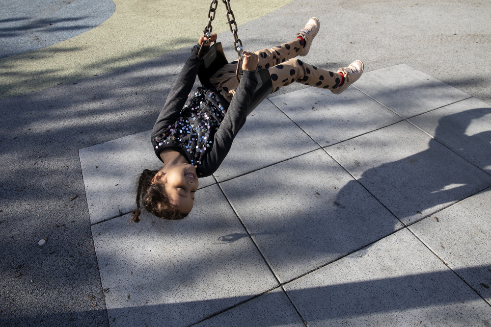 Skarleth Fernandez Flores, 6, spins on a swing at Dunbar Park Wednesday, May 23, 2018, in Chicago. The Flores family left their home country of El Salvador years ago due to gang violence, living in Guatemala for awhile before ending up in Mexico. They crossed the border into the United States as part of a caravan of hundreds of people, organized by Pueblo Sin Frontreras, where they surrendered and sought asylum. Pueblo Sin Frontreras worked with Showing Up for Racial Justice, a national network of activists, to find sponsor families, like the DeMay-Gres family in Chicago, to house those in the caravan who did not have relatives in the United States. (Erin Hooley/Chicago Tribune)