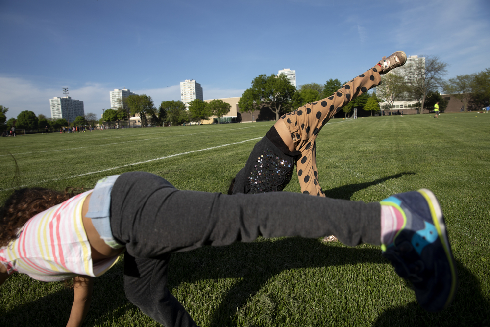 Sisters Perla Flores Delgado, 3, left, and Skarleth Fernandez Flores, 6, do cartwheels at Dunbar Park Wednesday, May 23, 2018, in Chicago. The Flores family left their home country of El Salvador years ago due to gang violence, living in Guatemala for awhile before ending up in Mexico. They crossed the border into the United States as part of a caravan of hundreds of people, organized by Pueblo Sin Frontreras, where they surrendered and sought asylum. Pueblo Sin Frontreras worked with Showing Up for Racial Justice, a national network of activists, to find sponsor families, like the DeMay-Gres family in Chicago, to house those in the caravan who did not have relatives in the United States. (Erin Hooley/Chicago Tribune)