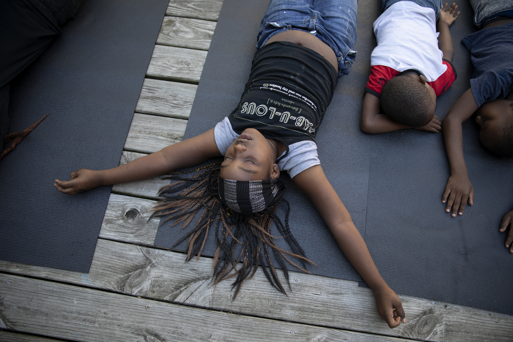"Rinaya Buick, 9, meditates during yoga class at the Yoga Gardens space Wednesday, June 27, 2018, in the Lawndale neighborhood of Chicago. Indigo Monae, who leads many of the yoga classes, often speaks of the importance of a ""sense of self,"" something she teaches through meditation. ""It's very meaningful, because if you don't have a sense of self, like, how are you going to love yourself? You know, if you don't know who are you, how do you know how to love yourself?"" she said. (Erin Hooley/Chicago Tribune)"
